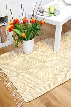 Hempeän valoisassa matossa on heitetty vuorotelleen valkoinen, beige ja oranssinkeltainen kude. Perinteinen mattomalli Tähkä (3470) on Mallikerrassa nro 1/2014.