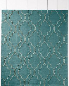 Handwoven in wool, this rug is hand-stitched with slender lines to create a quatrefoil pattern that resembles interlocked lattice and stylized tiles. A classic update to any room and decor, the clean motif lends a modern spin to the geometric trend that has become so popular in floor coverings.