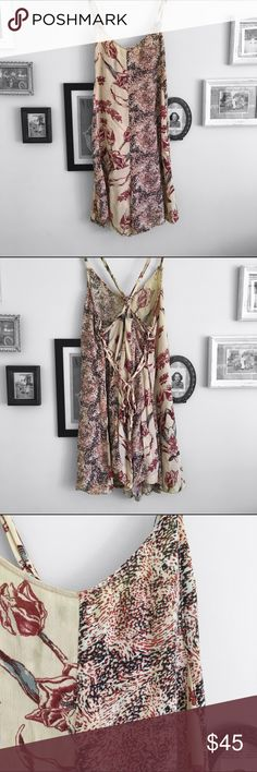 Free People Romper Free People Romper. Half floral, half a speckled pattern. One of the straps ripped, but it's tied back and should stay in place. Everything else is in good condition. Crosses in the back.  ⭐️10% off 2+ bundle  ⭐️Size Small ⭐️Smoke free home  ⭐️No stains Free People Dresses Mini