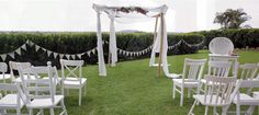 Byron Bay wedding ceremony at The Fig Tree. White mismatched chairs and Arbour