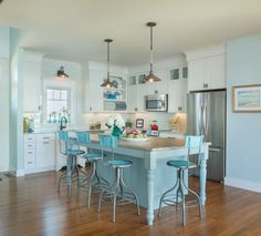Coastal kitchen with a fun turquoise color palette and adjustable metal stools