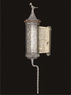 AN ESTHER SCROLL, MEGILLAH ESTER,  UNMARKED, PROBABLY TURKISH OR BALKAN, 19TH CENTURY,  The cylindrical body alternately pierced & engraved with scrolling foliage, with ropework band at top & bottom, coral beads secured by wire around the rim, pannelled conical top surmounted by bird finial, the silver mount attached to the scroll itself applied with a serpent, traces of gilding to the serpent & the finial, Hebrew inscription around base pronouncing the piece a gift to Yosef Chaim Yalooz