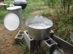 The Super Canner: this baby can fit almost 20 jars at a time. Simply constructed with cinder blocks, a galvanized tub and a blow torch. Did a hole to set the blow torch in, you can put an elbow on it to shoot it upward, I believe.  Different ways to do it.