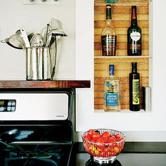 Go vertical: This family converted an ironing-board nook into a liquor cabinet, and mounted a wall rack to store their wine. You could also make a niche between wall studs.