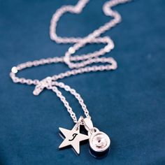 A beautiful silver charm necklace. This personalised necklace features a cool silver little gemstone charm and a cute little initial star. Hung