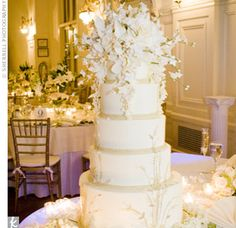 Cake baker to the stars, Sylvia Weinstock, designed Kellie and Lorenzo's beautiful confection. The cake was perfectly coordinated with Kellie's gown, right down to the gold Italian lace in her skirt. The same flowers used in the centerpieces top...