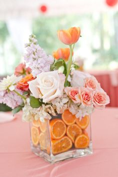sliced oranges to add a pop of color to this elegant flower scheme. The oranges also cover up the floral foam used to construct this gorgeous centerpiece.