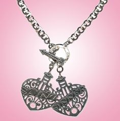 "Saint and Sinner Silver Filigree Toggle Necklace by Eldorado Club - This elegant  toggle necklace hangs from a  18 inch silver plate chain with a pair of dangling ornate filigree heart pendants, one reading ""Saint"", the other reading ""Sinner"" that measure approximately 11/2 inch by 1 1/12 inch .  Silver plated Toggle clasp."