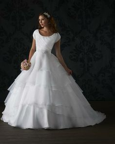 Totally Modest  - Cameo - This modest gown is sweet and demure with its asymmetrical ruched short sleeve bodice. Wispy layers of organza fall from the banded waistline and down the A-line skirt and train.  Fabrics: Organza
