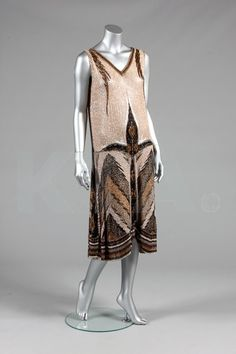 A beaded flapper dress, circa 1928, labelled made in France, size 44, the beige muslin ground with gold and black bugle beaded designs, hem pointed to the sides, bust 92cm, 36in