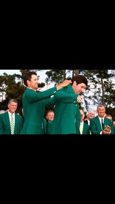 Adam Scott helping Bubba Watson put on his 2nd green jacket. #Masters2014