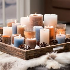 Verschillende kaarsen op een dienblad, en decoreer met dennenappels (winters gevoel = gezellig)