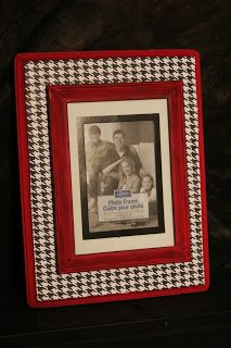 DIY Stacked Picture Frame  The backing is a wooden plaque from Michael's.  I painted edges crimson and modpodged houndstooth scrapbook paper over top.  The actual frame is from the Dollar Tree. I painted it red.  To attach the frame to wooden plaque,I knew I wanted something that would let me replace the picture.  Hot gluing the frame would not work.  Instead I used velcro circles on each of the four corners.  That way I can take the frame off and change pictures in and out.