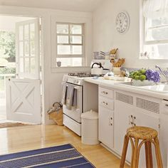 Wall-to-wall white gives this kitchen a fresh look while small pops of blue add a nautical undertone. | Coastalliving.com