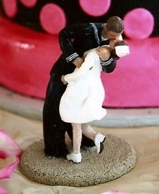 This custom wedding cake topper from http://weddingsculptures.com was inspired by the famous World War II photo of the sailor kissing a nurse!  As you see, not all cake toppers have to be displayed on the cake!