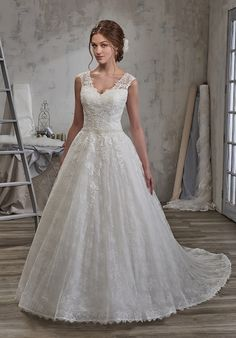 cap sleeves, beaded waist line, sheer back, lace appliques, and back with zipper and buttons