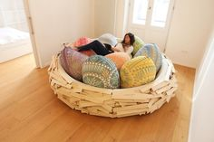 A woman lounges in a bird's nest turned sofa designed by OGE CreativeGroup