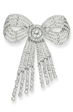 A BELLE EPOQUE DIAMOND BOW BROOCH, BY CARTIER  Designed as a ribbon bow composed of four diamond lines to the central circular-cut diamond cluster and diamond collet tassels, circa 1910, 5.5 cm long Signed Cartier, Paris