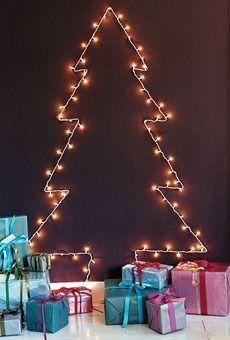 Árvore feita com cordões de luzes e ganchos adesivos colados na parede