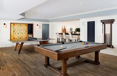 Under a tray ceiling accented with blue, this well appointed game room boasts a pool table and ping pong table and shiplap walls holding a chalkboard beside a custom built-in bar seating ivory upholstered barstools.