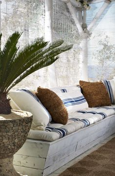 Ralph Lauren Home creates a shady beach retreat with bench cushions and throw pillows sewn from classic blue and white striped textiles.