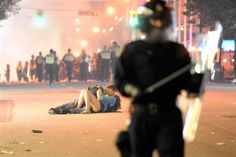Incredible shot by Getty Images photographer Rich Lam last night (June 15, 2011) during post-Stanley Cup loss in Vancouver BC when riots broke out. This couple makes their statement about the pointlessness of rioting withwith some peace and love! :)