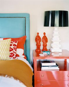 Upholstered headboard, turquoise and orange accents.  Black shade add depth.