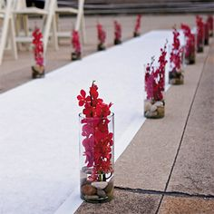 Red Orchid and Stone Aisle Decor. The 6 p.m. ceremony took place outdoors on the grounds of the Chicago History Museum. The aisle runner was lined with vases filled with river rocks and mokara orchids also designed by A.Vision Chicago.
