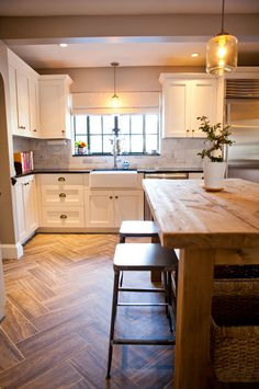 Lots of elements I love here. The dark counter tops, the white cabinets, herringbone floors, warm woods.