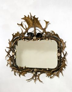 Mirror ca. 1860 Germany | Rampendahl, H. F. C. | Although this mirror is set on a base of carved wood, it is largely made up of stag horns from two different species of deer, arranged with goat horns and boar tusks. Such furniture, which may seem rather gruesome to modern taste, was extremely fashionable in the middle of the 19th century. / V & A