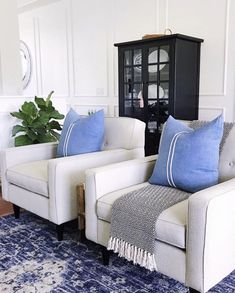 Living room decor with blue and white striped pillows, blue vintage rug, black cabinet, white painted walls with panel molding, fiddle leaf fig and modern chairs - how to choose a design style - jane at home Coastal Living Rooms, My Living Room, Living Room Furniture, Living Room Decor, Rustic Furniture, Antique Furniture, Furniture Stores, Coastal Cottage, Coastal Homes