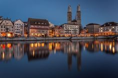 On a Mild Winter Evening in Zurich The old town of Zurich with the Grossmünster church reflected on the river Limmat at dusk Switzerland. City Architecture, Travel Information, Travel And Leisure, Old Town, Travel Guides, Switzerland, Beautiful Places, Around The Worlds, River