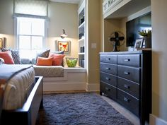 A striped focal wall and sporty accents stand out in a comfy bedroom designed for a growing kid.