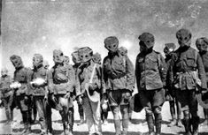 Soldiers in gas masks during World War I (viaState Library Queensland)