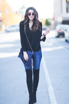 These over the knee boots look cute worn with a fringed scarf and simple V neck blouse. Via themiddlecloset. Jeans: Frame Denim, Boots: Stuart Weitzman, Bag: Sole Society