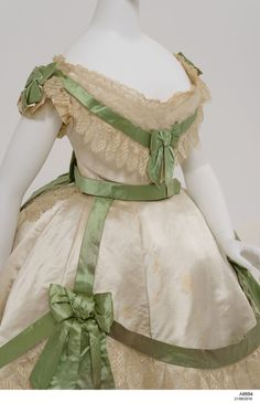 Cream silk and lace wedding dress comprising a long full skirt, a cap sleeve bodice, a long sleeve bodice, green pearl-decorated silk belt, bow detail belt and a small lace rosette.