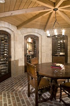 With reclaimed brick flooring, stone walls with hand carved details, site-cut oak beams, and three interconnected wine cellars, this ratskellar is one of the more unique spaces in this French Provincial estate built by Stonewood LLC.