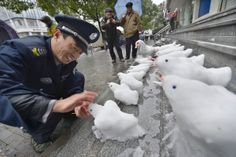 Security guard Du Jinqian makes snow birds on the steps in front of a bank where he works on February 19, 2013 in Hangzhou, China. Around the World in 11 Photos