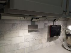 Adorne modular lighting system. Love it - doesn't junk up your backsplash with outlets and you can add docking stations for technology. Very clean!
