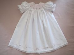 This sweet hand smocked and hand embroidered dress truly is precious. Made of soft white cotton fabric with delicate pink smocking and beautiful rose embroidery adorning the round yoke. Delicate lace trims the short puffy smocked sleeves and hem. Smocked Baby Dresses, Baby Girl Dresses, Cute Dresses, Beautiful Dresses, Flower Girl Dresses, Baby First Birthday Dress, Collars, Little Pink Dress, Rose Embroidery