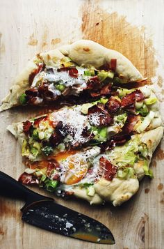 Breakfast pizza with leeks, bacon and runny eggs.