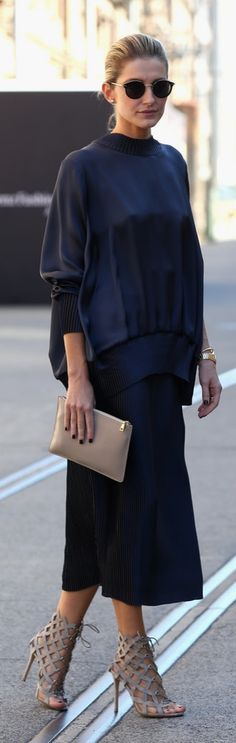 Australia Spring/Summer street style: a sleek black sating sweatshirt and black culottes with cutout heeled sandals, a tan clutch and sunglasses