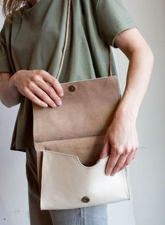 The cream and tan details of Awl snaps minimalist crossbody look great with earth tones.