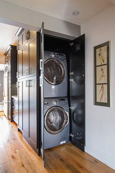 A washer and dryer are hidden within plain sight in this clever kitchen cabinet configuration.