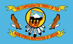 """The banner-like flag is light blue (sample flag provided by Elmer's Flag & Banner, Portland, Oregon) with a yellow ribbon across the top with """"THE CONFEDERATED TRIBES OF THE"""" and a similar ribbon across the bottom with """"WARM SPRINGS RESERVATION OF OREGON"""", both in red. Between the ribbons are two flying eagles in brown and white, approaching the center from either side."""