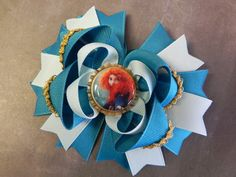 Brave Merida Boutique Layered Bottle Cap Hair Bow - OTT over the top - Disney Pixar Princess - blue, gold - by sweetteabowtique. $7.50, via Etsy.
