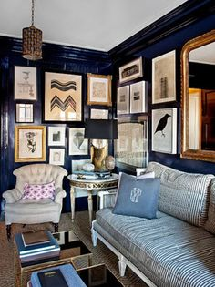 eclectic frames, dark walls, dark mouldings.. just lovely