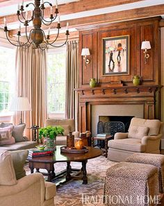 Ceiling beams and wood paneling set the stage and the tones are echoed in the chandelier and table. All of the wood is then complimented by the soft mocha tones in the upholstered furniture, creating a warm, comfortable room.