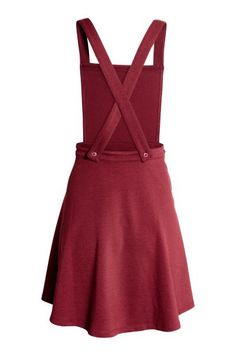 Vestido peto de punto: Vestido peto corto en punto grueso. Tirantes anchos que se cruzan en la espalda, cintura entallada, falda con ligero vuelo y cremallera oculta en un lateral.