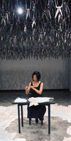 A woman sits silently mending beneath a cloud of 1500 viciously sharp scissors. The Mending Project by Beili Liu. #art